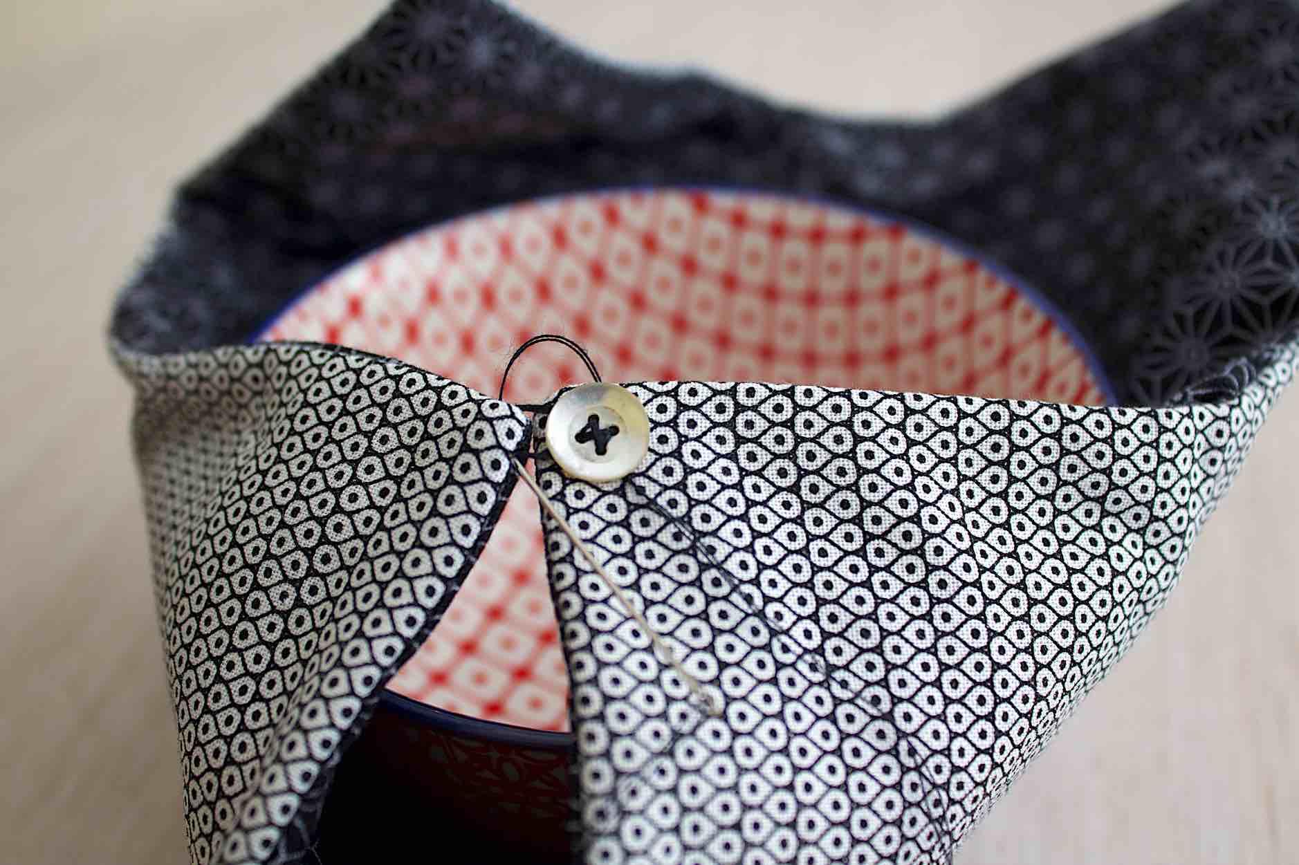 cucire ad un angolo un bottone in madrreperla